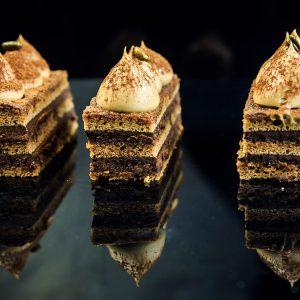 tasty chocolate opera cake slices decorated with white cream on black mirror background
